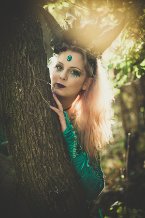 portrait of fantasy  fairy with horns in forest among  trees and branches