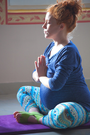 red head pregnant young woman on yoga class indoor meditation
