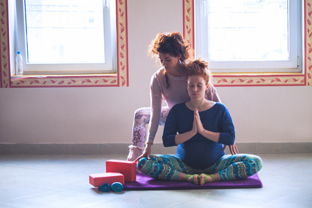 red head pregnant young woman on yoga class with instructor assisting