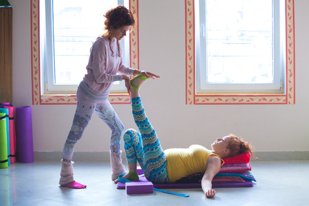 red head pregnant young woman on yoga class indoor with instructor assisting Standard-Bild