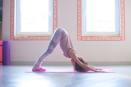 young woman practice yoga indoor full body shot side view