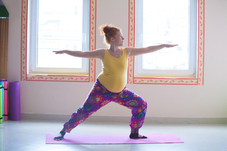 red head pregnant young woman practice yoga indoor side view