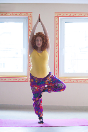 red head pregnant young woman practice yoga indoor front view