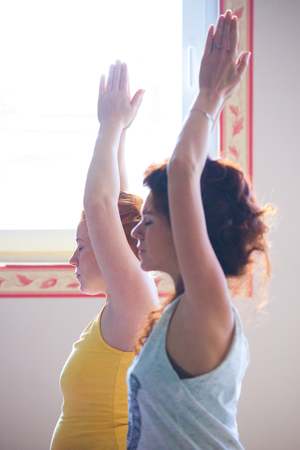 pregnant young woman on yoga class indoor with instructor