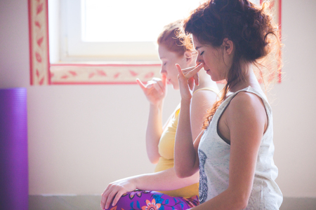 closeup of couple of women on yoga class exercises breathing technique healthy lifestyle concept indoor