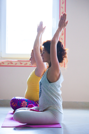 red head pregnant young woman on yoga class indoor with instructor