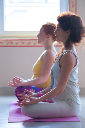 Pregnant young woman on yoga class indoor with instructor side view meditation