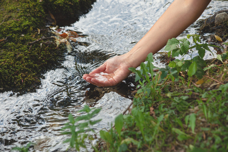 woman hand with water from a pure mountain stream closeup healthy lifestyle concept