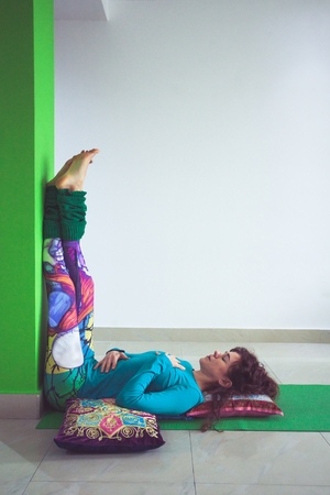 young woman in yoga relaxing pose with legs up the wall side view indoor Standard-Bild