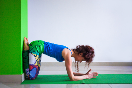 young woman in yoga position against wall indoor full body shot Standard-Bild