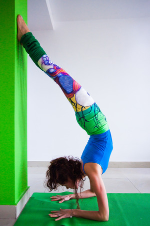 woman practice handstand against wall yoga class indoor side view