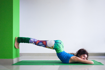 young woman practice yoga indoor pose against wall