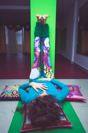 young woman in yoga relaxing pose with legs up the wall  indoor Standard-Bild