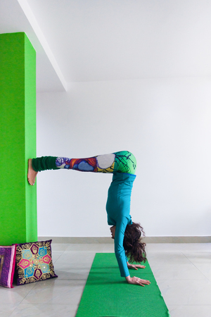 young woman practice yoga indoor  handstand  against wall