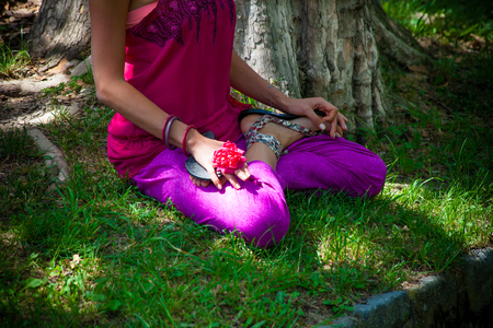 lower woman body in lotus yoga posture outdoor practice in park by the lake summer day