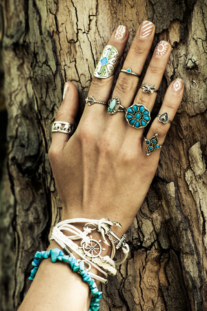 closeup of woman hand on tree surface  with lot of boho style jewrly, rings and bracelets outdoor summer day