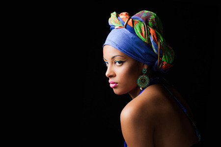 African black young woman beauty portrait with colorful turban headscarf studio shot on black Standard-Bild
