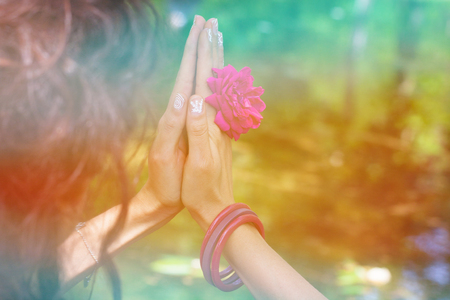woman hands with flower in yoga mudra gesture outdoor in nature closeup summer day in front lake 스톡 콘텐츠