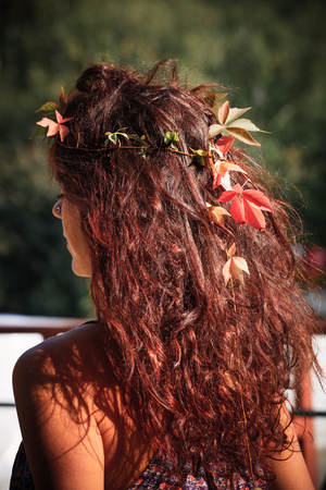 shiny curly  healthy woman reddish hair with autumn leaves on autumn sun outdoor