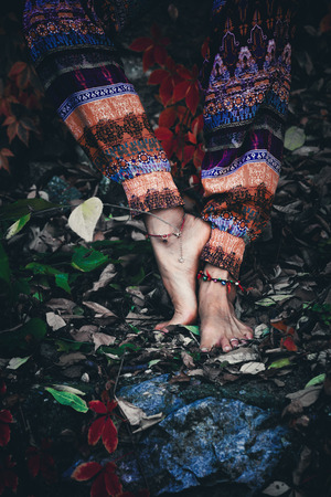 woman practice yoga outdoor closeup  barefoot  on autumn leaves on ground  balance pose