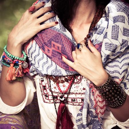 Nahaufnahme der Frau in Kleidung und Schmuck im Boho-Stil, Armbänder, Halskette und Ringe im Freien Sommertag