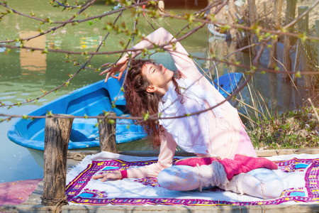 young woman practice yoga outdoor spring day by the lake