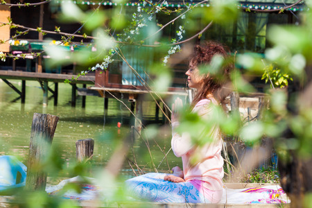 young woman practice yoga outdoor spring summer  day by the lake sit in lotus position with hands in anjali mudra Stok Fotoğraf