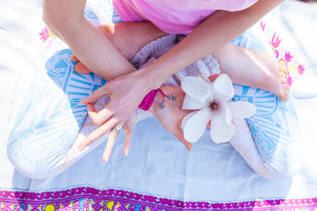 woman in symbolic yoga lotus posture hold flower in one hand and other hand in mudra gesture from above outdoor spring summer day