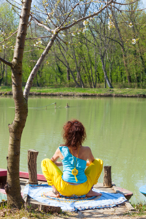 young woman practice yoga outdoor by the lake healthy lifestyle concept back view full body shot Imagens