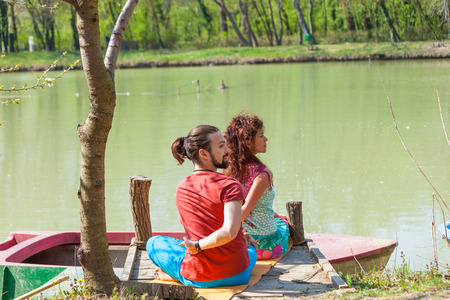 young man and woman practice yoga outdoor by the lake sunny summer day