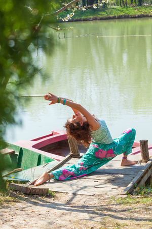 young happy woman practice yoga outdoor by the lake healthy lifestyle concept sumer day full body shot Stock Photo