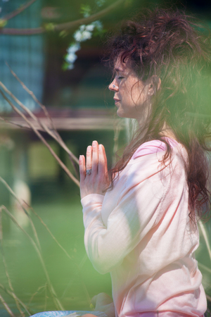 young woman practice yoga outdoor spring summer  day by the lake sit  with hands in anjali mudra