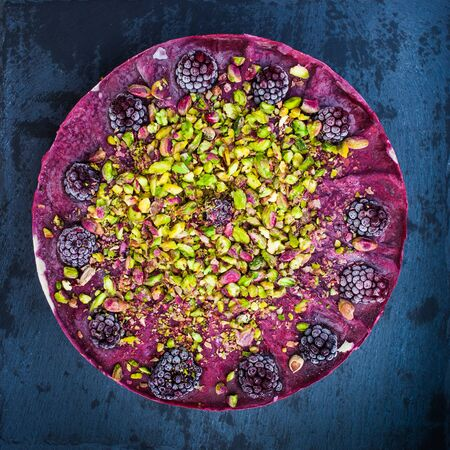 healthy no sugar raw cake with blackberries and pistachios flat lay on dark granite background healthy food concept