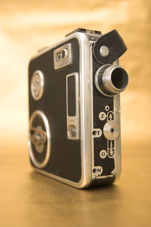 Old 8mm film camera on dirty gold background