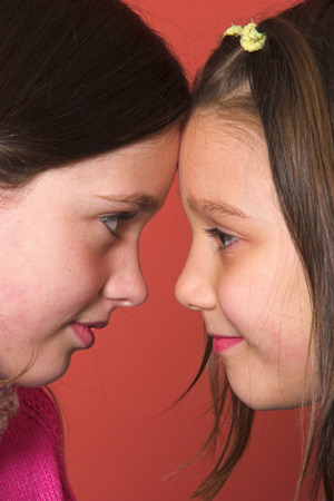 Two young girls facing each other and touching foreheads