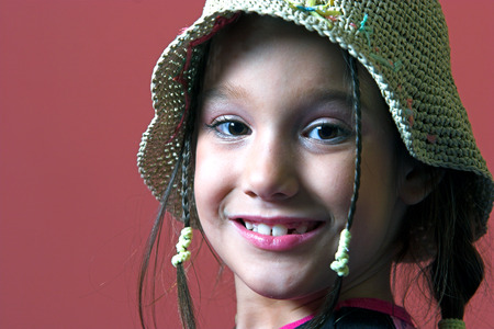 tresses: Young girl with tresses and a hat smiling