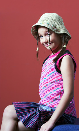 Young girl with tresses and a hat sitting Stock Photo