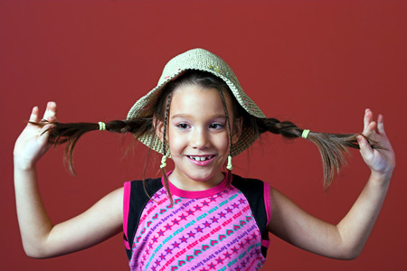 tresses: Young girl holding her tresses and similing