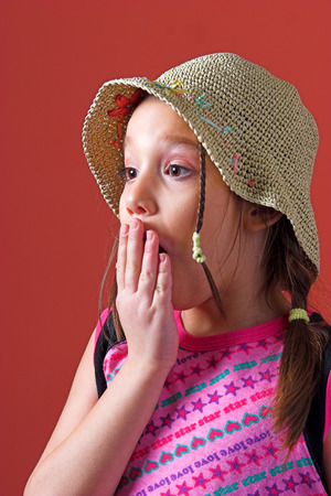tresses: Surprised young girl with tresses and a hat, holding a hand on her mouth Stock Photo