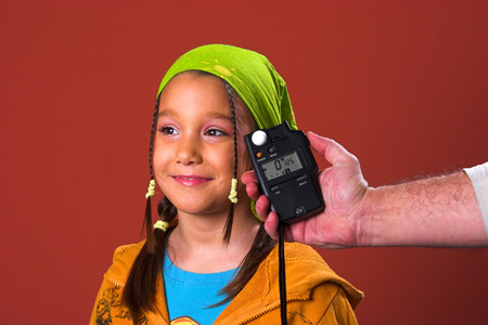 Male hand holding a flash meter on a young girl photo