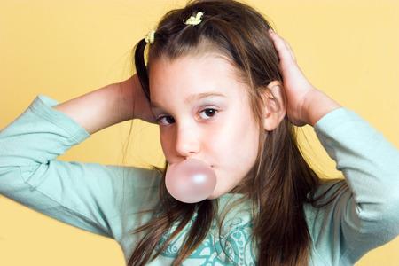 -Guma do żucia: Młoda dziewczyna dokonywania bańki z gumy do żucia i stanowiących