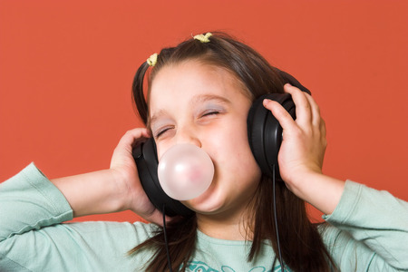 Young girl enjoying the music and making a bubble from chewing gum