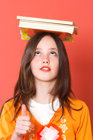 Girl with books on her head holding thumb up