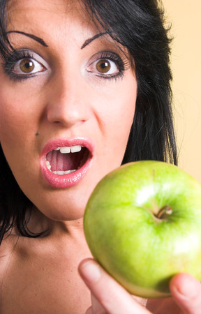 Young woman making funny faces and holding a green apple Stock Photo - 1470657