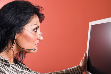 Surprised woman with headset looking at the computer monitor