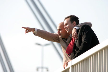 Two businessmen standing on bridge Stock Photo