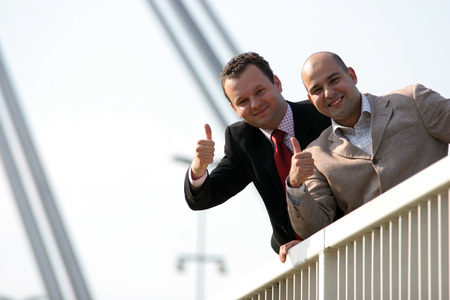 Businessmen standing on bridge and holding thumbs up Stock Photo