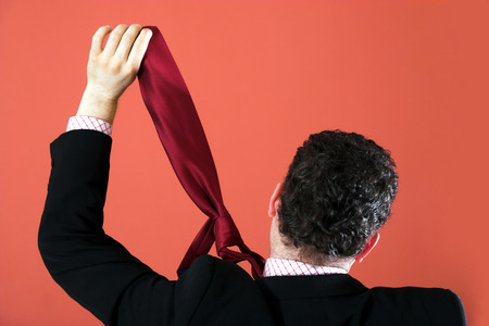 Businessman hanging himself with a tie Stock Photo