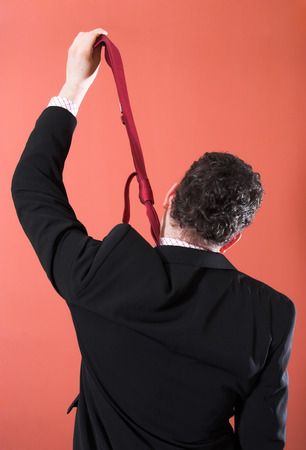 Businessman hanging himself with a tie photo