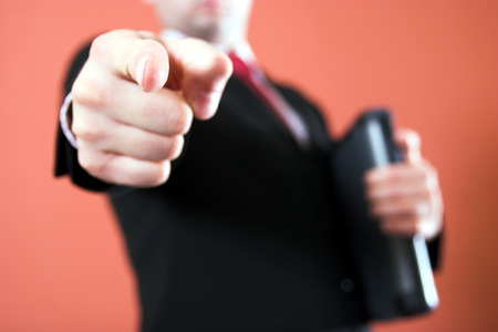 Businessman with laptop pointing to the viewer Stock Photo - 1567754